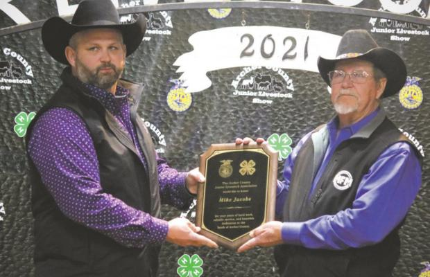 Keith McCall (left) presents a plaque to Mike Jacobs for his service to the Archer County Junior Livestock Show. Photo/Jerry Phillips
